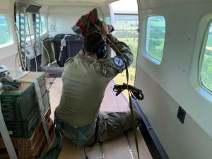 A view from within the aircraft shows an instructor preparing to toss the SATB while the aircraft is aloft.