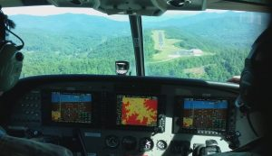 A view from the cockpit as the aircraft approaches a mountain landing strip